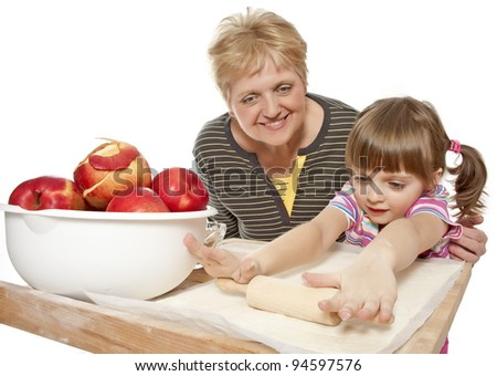 grandmother teaching her granddaughter bake apple pie - stock photo