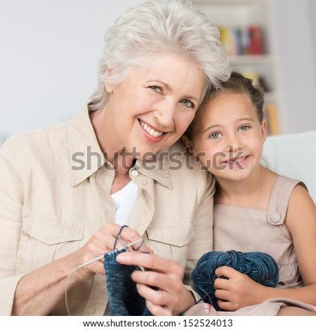 Grandmother teaching her pretty smiling little granddaughter to knit as they sit close together on a sofa in the living room - stock photo