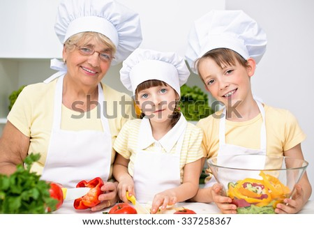 grandmother with grandchildren holding different vegetables and preparing a salad - stock photo