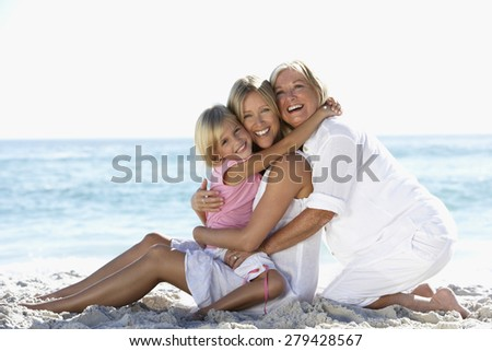 Grandmother With Granddaughter And Daughter Relaxing On Beach - stock photo