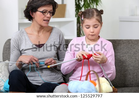 Grandmother with granddaughter knitting - stock photo