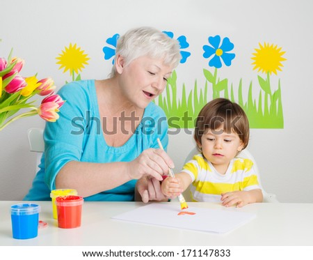 Grandmother with grandson learning drawing at home - stock photo