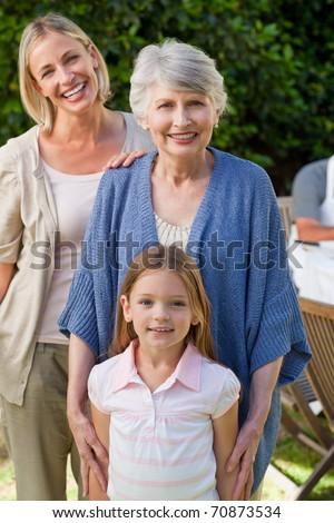Grandmother with her daughter and grand daughter looking at the camera in the garden - stock photo