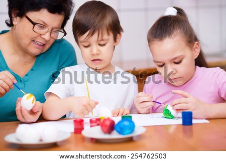 Grandmother with her grandchildren are coloring eggs for Easter, indoors - stock photo