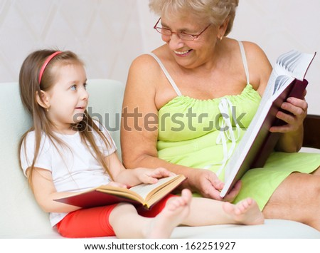 grandmother with her granddaughter are reading a book at home - stock photo
