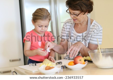 Grandmother with little girl in kitchen baking cookies  - stock photo