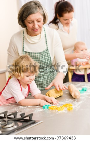 Grandmother with little girl prepare dough for baking cookies - stock photo