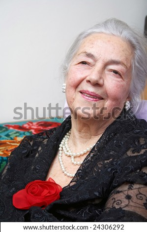 Grandmother with silk red rose - stock photo