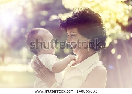 Grandmother with small baby smiling in the outdoors - stock photo