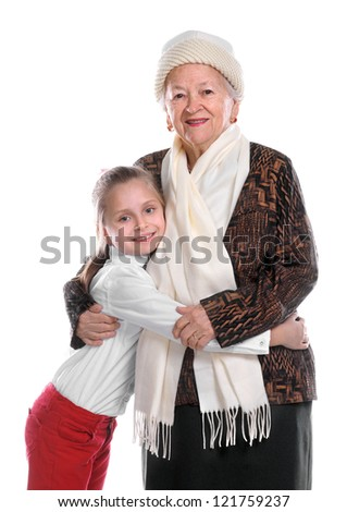 Grandmother with young girl smiling and embracing one another on white background - stock photo