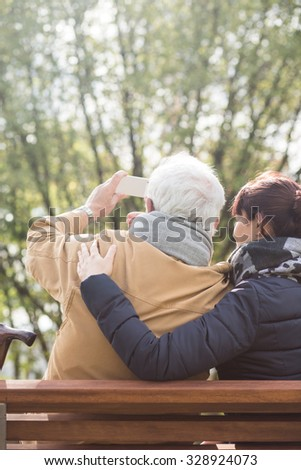 Grandpa and granddaughter taking picture in the park - stock photo