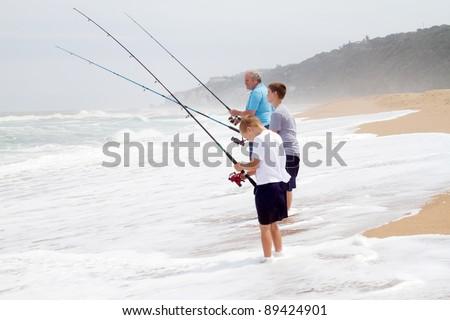 grandpa and grandsons fishing on beach - stock photo
