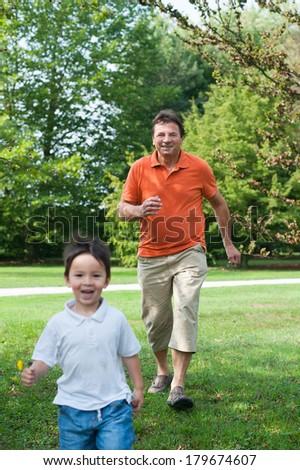 Grandpa and his grandson are having fun in the park - stock photo