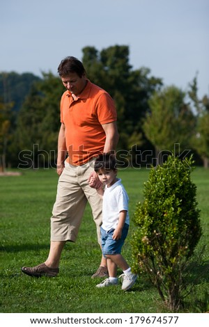 Grandpa and his grandson are walking in the park. - stock photo