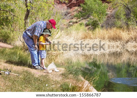Grandpa fishing with his grandson at a beautiful lake - stock photo