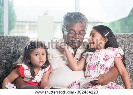 Grandparent and grandchildren reading story book together. Happy Indian family at home. Asian grandfather and granddaughters indoor lifestyle. - stock photo