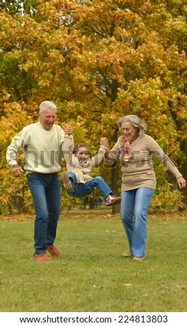 Grandparents and grandchild together in autumn park - stock photo
