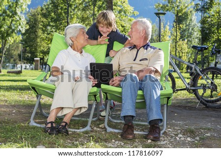 Grandparents and grandchild using tablet computer to video chat while camping - stock photo