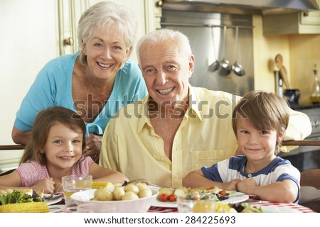Grandparents And Grandchildren Eating Meal Together In Kitchen - stock photo
