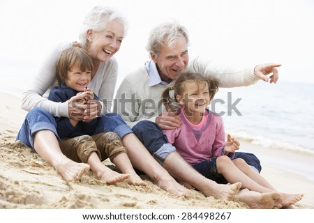 Grandparents And Grandchildren Sitting On Beach Together - stock photo
