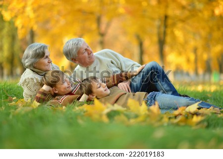 Grandparents and grandchildren together in autumn park - stock photo