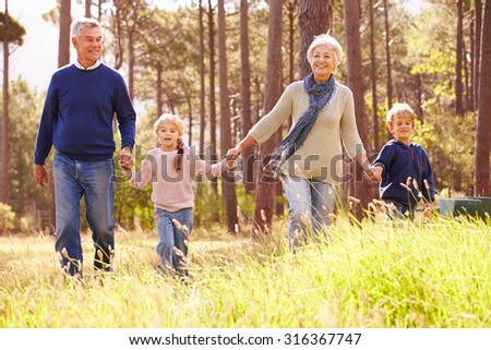 Grandparents and grandchildren walking in the countryside - stock photo