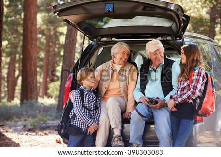 Grandparents and grandkids at the back of car before hiking - stock photo