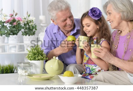 grandparents  and  little girl with tea - stock photo