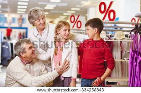 Grandparents and their grandchildren shopping in the mall - stock photo