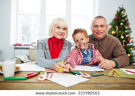 Grandparents and their grandson with crayons looking at camera while drawing - stock photo