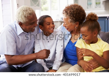 Grandparents and their young grandchildren relaxing at home - stock photo