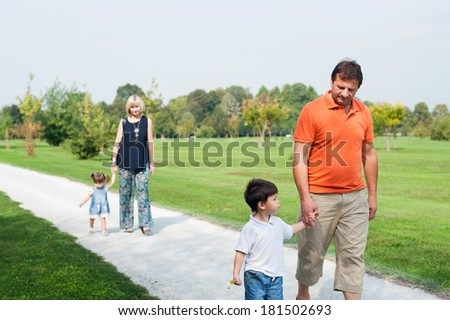 Grandparents are walking on country road with their grandchildren. - stock photo