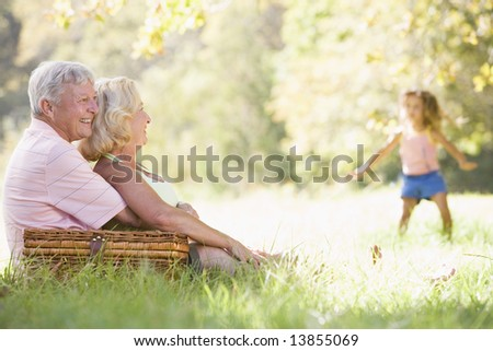 Grandparents at a picnic with young girl in background dancing - stock photo