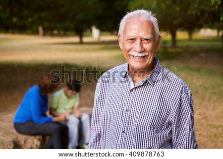 Grandparents educating grandson: Senior woman and old man spending time with their grandchild in park. The old people help the preteen boy doing his school homework. The grandpa looks at camera  - stock photo