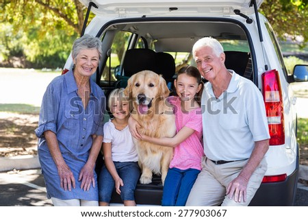 Grandparents going on road trip with grandchildren on a sunny day - stock photo