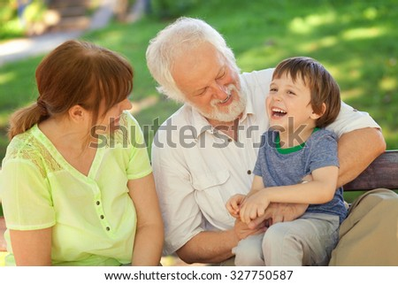 Grandparents having great fun with their grandchild - stock photo