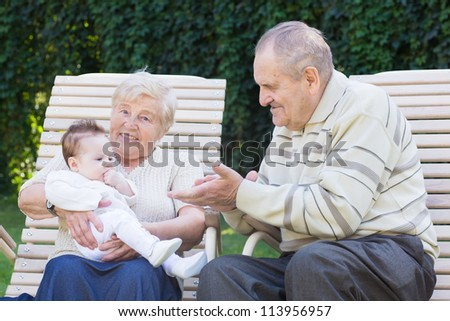 Grandparents playing with a little baby girl outside in the garden - stock photo