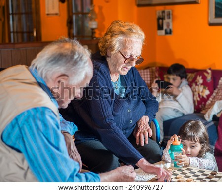 Grandparents playing with granddaughter indoor. - stock photo