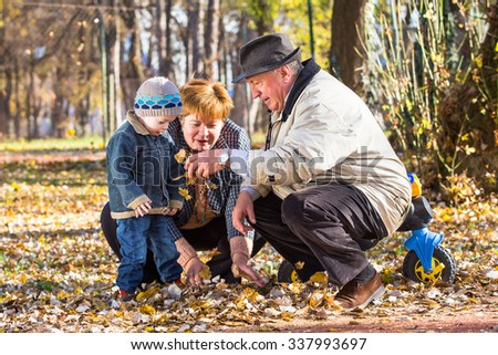 grandparents playing with grandson in a park - stock photo