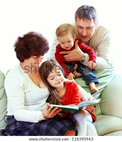 grandparents reading books to beautiful grandchildren - stock photo
