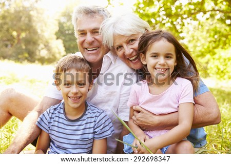 Grandparents sitting outdoors with their grandchildren - stock photo
