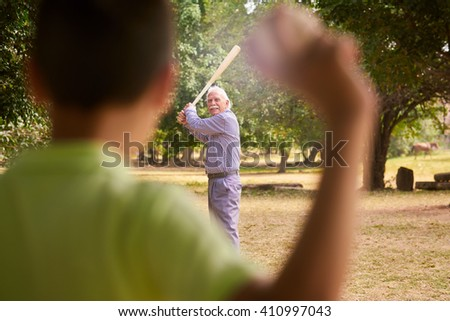 Grandparents spending time with grandson: Senior man playing baseball with his grandson in park. The old man holds the bat, while the kid prepares to throw the ball - stock photo