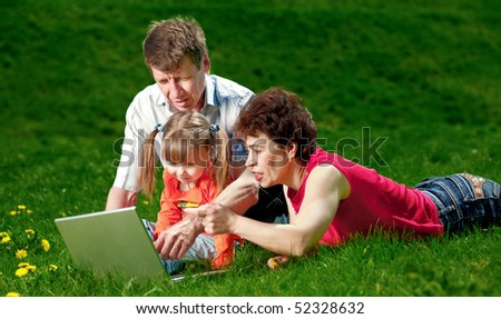 Grandparents with child sit in grass and look at laptop - stock photo