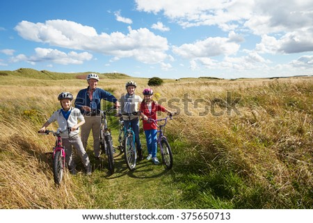 Grandparents With Children Cycling Through Countryside - stock photo
