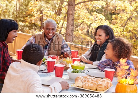 Grandparents With Children Enjoying Outdoor Meal - stock photo