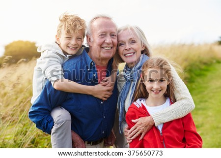 Grandparents With Children On Walk Through Countryside - stock photo