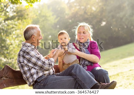 Grandparents with grandson enjoying the sunny autumn day in park. - stock photo