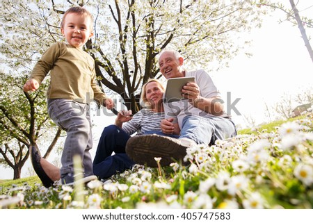 Grandparents with grandson enjoying the sunny spring day outdoors. - stock photo