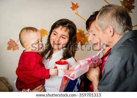 Grandparents with their small grandchild celebrating first birthday at home - stock photo