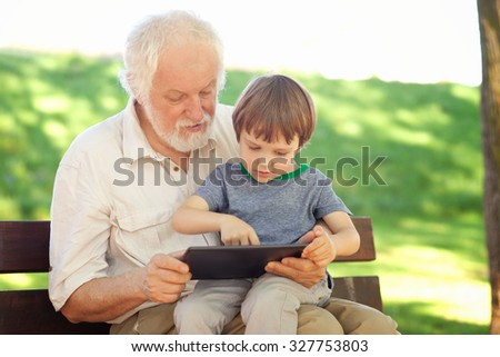 Grandson and grandfather using tablet in the park, shallow depth of field - stock photo